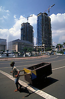 In Jakarta, Indonesia, a construction worker pulls a cart through city streets lined with tall, modern skyscrapers. roadways, occupations, trades, cityscape. Skyscrapers & carts. Jakarta, Indonesia central city.