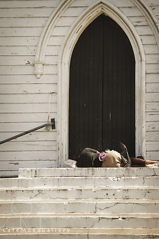 Vagrant on the steps, asleep,  outside the arched black doorway of the Anglican cathedral