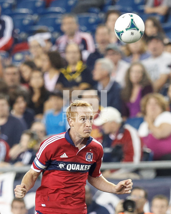 Chicago Fire midfielder Jeff Larentowicz (20) heads the ball.  In a Major League Soccer (MLS) match, the New England Revolution (blue) defeated Chicago Fire (red), 2-0, at Gillette Stadium on August 17, 2013.