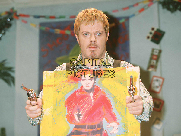EDDIE IZZARD..A Day In The Death Of Joe Egg Photocall   ..Ref: 11309..elvis painting, guns, art, goatee, mustache, half length, half-length..www.capitalpictures.com..sales@capitalpictures.com..©Capital Pictures..