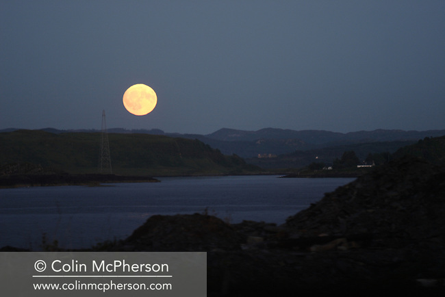 A full moon rising above the islands of Seil and Luing, two Inner Hebridean islands on Scotland's west coast.