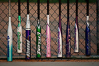 Softball bats in a variety of bright colors hang inside the fenced dugout during a youth softball game in Westerville, OH.
