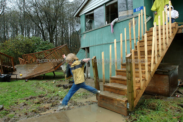 11/10/2006--Hamilton, WA, USA..4 year old Dennis Peterson jumps over pools of water in front of his family's  flood damaged home in Hamilton, Wash., which tore away a deck the family had just built on their home. With a population of about 330 people, Hamilton is a  flood-prone town on the Skagit River that some local residents want the town moved away from the river...Photograph By Stuart Isett.All photographs ©2006 Stuart Isett.All rights reserved.