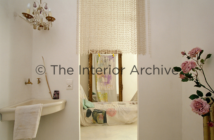 A daybed covered in a hand-painted textile is glimpsed through the open doorway of the bathroom