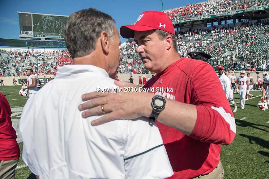 Wisconsin Badgers Head Coach Paul Chryst, right, shakes hands with Michigan State Spartans Head Coach Mark Dantonio during an NCAA college football game Saturday, September 24, 2016, in East Lansing, Michigan. The Badgers won 30-6. (Photo by David Stluka)