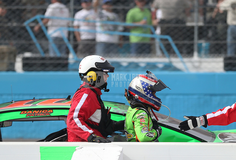 Mar. 3, 2013; Avondale, AZ, USA; NASCAR Sprint Cup Series driver Danica Patrick is tended to by safety crew members after crashing during the Subway Fresh Fit 500 at Phoenix International Raceway. Mandatory Credit: Mark J. Rebilas-