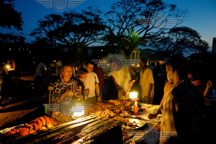 Tourists ordering a fish dinner from food stalls in the Forodhani Gardens in Stone Town. Formerly a local market, it is now dominated by tourists.