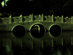 A stone bridge casts eerie reflections upon a lake.