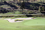 A green with a red flag marking the hole on a golf course during the fall season in Branson Missouri