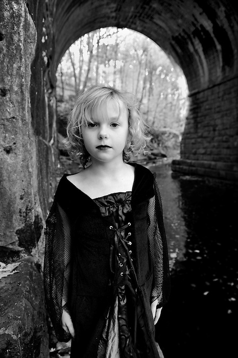A young girl in a Gothic dress standing in a tunnel