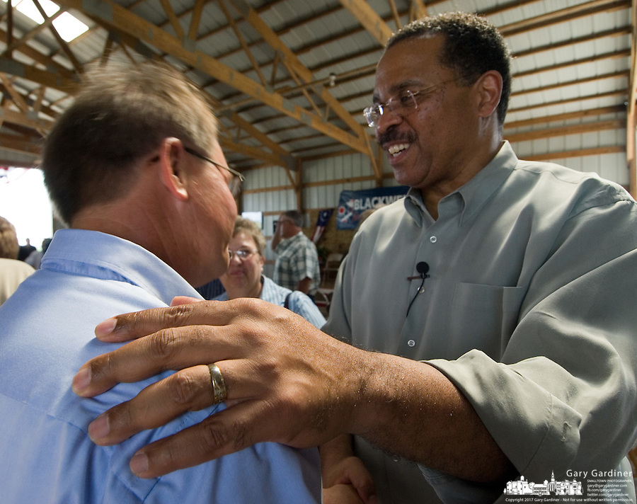 Republican gubernatorial candidate Ken Blackwell places his hand on the shoulder of a supporter as he shakes hands after a rally at a Sabina, Ohio, farm Saturday, Aug. 19, 2006.<br />