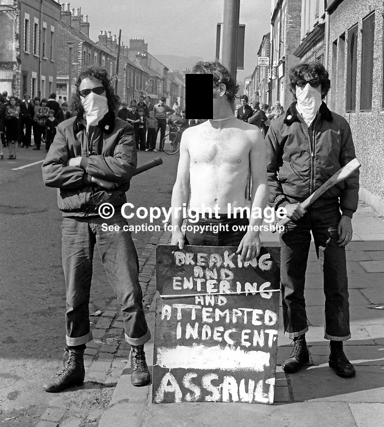 Rough justice - a young man is tied to a lampost and forced to hold a placard claiming that he was guilty of burglary and attempted sexual assault. His face was badly bruised and it was obvious that he had been badly beaten by the UDA punishment squad. The photo was taken in Berlin Street off the loyalist Shankill Road, Belfast, N Ireland. 2nd July 1972. 197207020401<br />