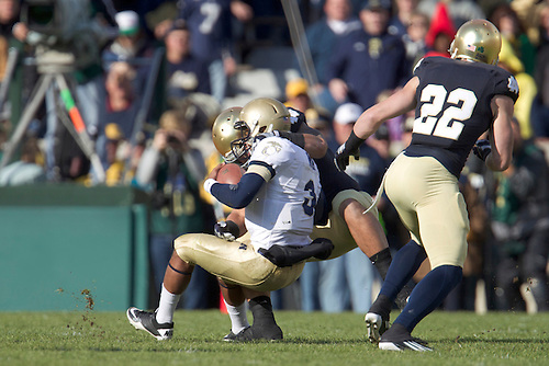 Notre Dame inside linebacker Manti Te'o (#5) tackles Navy quarterback Trey Miller (#3) during first quarter of NCAA football game between Notre Dame and Navy.  The Notre Dame Fighting Irish defeated the Navy Midshipmen 56-14 in game at Notre Dame Stadium in South Bend, Indiana.