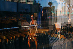 A woman is reflected in the American Apparel store window, located on Sunset Boulevard in the Echo Park neighborhood of Los Angeles, California February 6, 2015.
