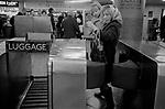 London underground train station ticket barrier, mother and child smoking.1970.
