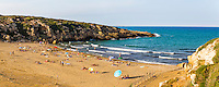 Calamosche Beach, panoramic photo of people sunbathing on the beach near Noto in the Vendicari Nature Reserve, South East Sicily, Italy, Europe. This is a panoramic photo of Calamosche Beach, showing people sunbathing under sun umbrellas. Calamosche Beach is a popular, secluded beach near Noto in the Vendicari Nature Reserve, South East Sicily, Italy, Europe.