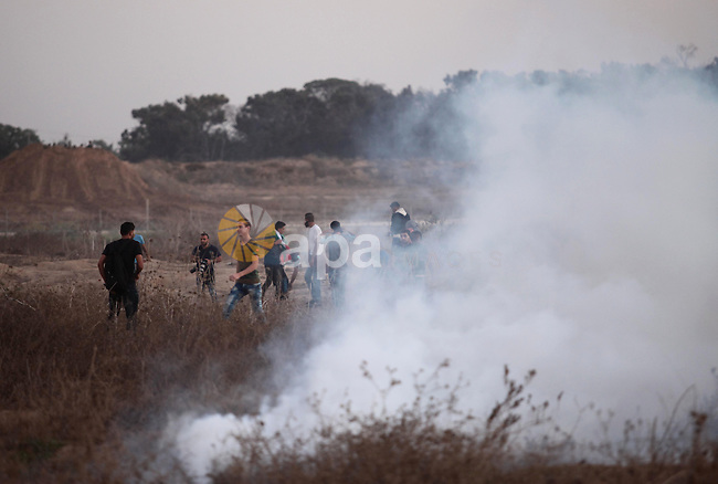 Palestinian protesters run for cover from tear gas during clashes with Israeli troops near a border fence between Israel and the Gaza Strip on October 14, 2015 east of Bureij in central Gaza. The outbreak of violence between Palestinians and Israeli forces in recent weeks has worsened in October, raising fears of a third intifada, or uprising. Photo by Ashraf Amra