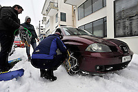 Pictured: A motorist install snow chains to his car in Ioannina, Greece. Wednesday 11 January 2017<br /> Re: Heavy snow has affected the town of Ioannina, northern Greece