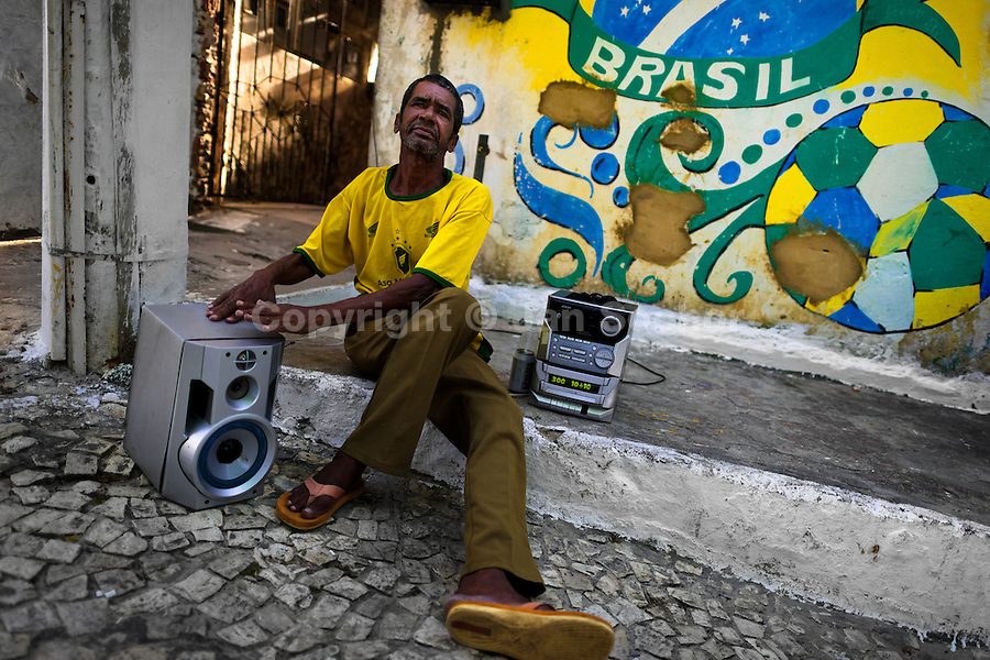 A Brazilian man, sitting in front of a mural celebrating Brazilian football, enjoys music playing on the street of Salvador, Bahia, Brazil, 9 February 2012.