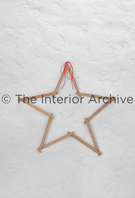 A simple star created from a foldable ruler decorates one of the whitewashed walls