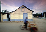 Passing a typical wooden house, a bicycler is a blur on the sandy roads of Isla de Holbox, Mexico.