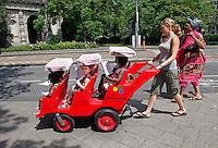 Vrouw loopt met kinderwagen vol peuters