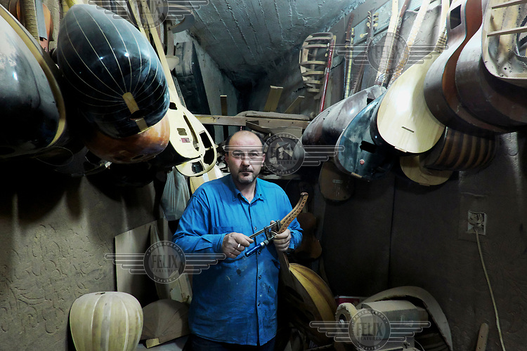 Kawa Isso in his workshop where he makes stringed instruments such as ouds, buzuqs and guitars.  He used to live in Aleppo where, for 14 years, he had also made stringed instruments.