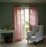 The sheer pink gingham curtains and a loose cover fashioned out of red and white tea towels are perfect for this simple country living room