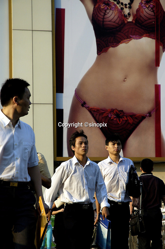What's on a modern Chinese man's mind. Office workers passing advertising image of young woman in underwear in Shenzhen, China. .
