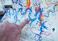 Shanon Lanphar (cq), Briceson Lanphar (cq, age 14) an Travis Lanphar (cq) with team Twisted Limbs from Haines City, Florida, look at a map of Table Rock Lake during the U.S. Open Bowfishing Championship, Saturday, May 3, 2014. <br /> <br /> Photo by Matt Nager