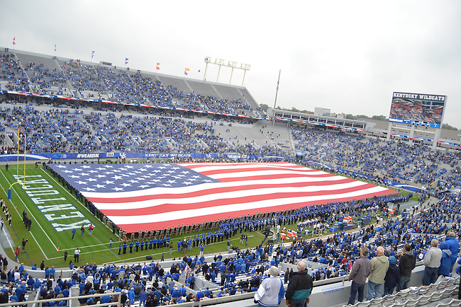 Veterans stretch a large flag over the field during the pregame Heroes Day ceremony before the University of Kentucky versus University of Louisiana at Monroe football game at Commonwealth Stadium in Lexington, Ky., on Saturday, October 11, 2014. Photo by Cameron Sadler | Staff