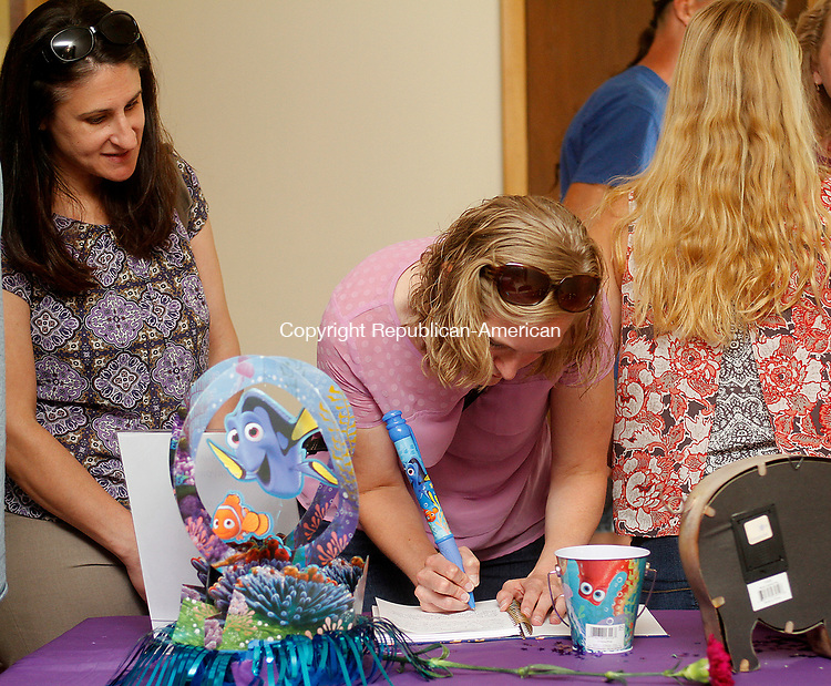 OXFORD, CT - 29 JULY 2017 - 072917JW12.jpg -- Former teachers of Chelsea Wheeler, Grace Olbrys watches as Heather Malash writes in the favorite memory book during the celebration of Wheeler's life Saturday at the Riverside Firehouse.  Jonathan Wilcox Republican-American