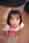 A young Asian girl looking up with a glum expression on her face, Estes Park, CO