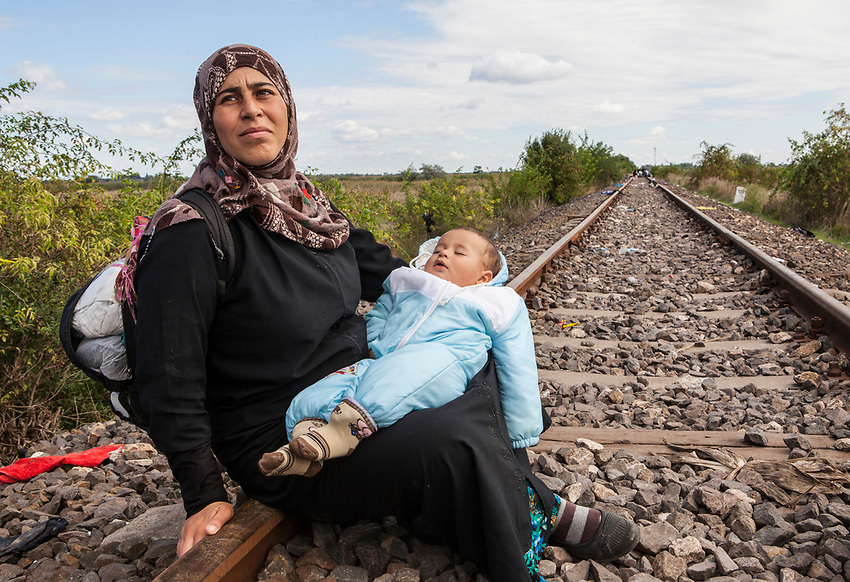 Farhah Ahmadi holds her baby boy while she rests on the railway line that is used as a crossing point between Serbia into Hungary by mostly Syrian refugees. Refugees at Roszke Crossing on Serbian-Hungarian Border.