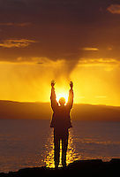 woman raising her arms to worship the setting sun in the San Juan Islands of Washington