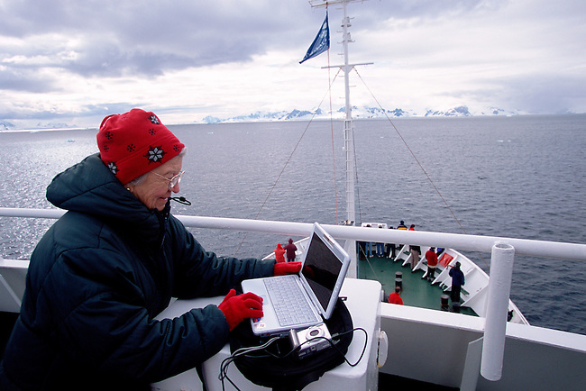 Silver surfer downloading a digital camera to a laptop computer on the deck of a tourist ship in Antarctica