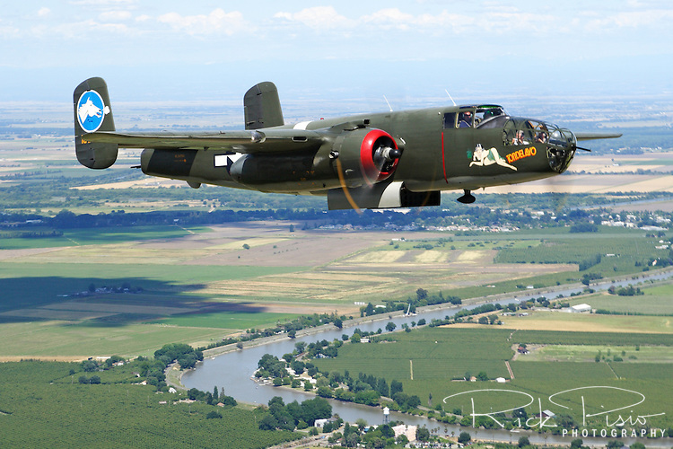 """The Collings Foundation B-25 Mitchell Medium Bomber """"Tondelayo"""" flies over California's San Jauquin Valley Delta as part of the Foundation's 2006 Tour. The B-25 first gained fame when it was used in the April 1942 Doolittle Raid, in which 16 B-25B's, led by the legendary Lt Col Jimmy Doolittle, took off from the carrier USS Hornet and successfully bombed Tokyo and four other Japanese cities. Powered by a pair of Wright R-2600 """"Cylone"""" radials, producing 1,850 horsepower each, the Mitchell could attain a maximum speed of 275 mph with a combat radius of 1,350 miles. Serial #44-28932 is a J model of the Mitchell. Earlier models were modified with a shorter nose that was packed with machine guns and cannon designed for low level strafing missions. The J model reverted back to the original glass nose section that was used in the original models."""