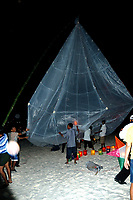 Giant paper lantern being lit on a beach in Thailand on new year's eve - paper lanterns are the traditional way to see out the new year and honour one's dead
