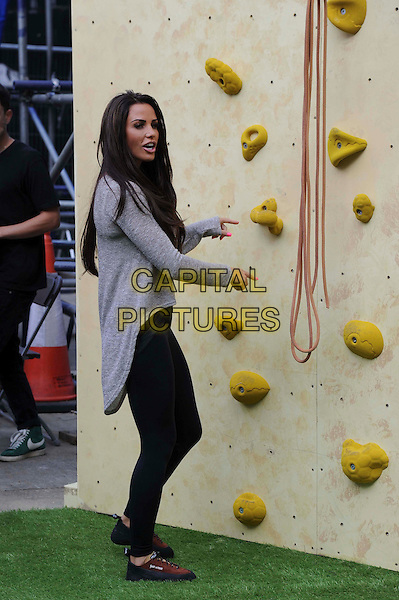 Katie Price (Jordan) .Walkers Crisp Deep Ridged Launch Climbing Wall at Truman Brewery, London, England..August 29th, 2012.full length grey gray top black leggings  side hands arms mouth open.CAP/CAS.©Bob Cass/Capital Pictures.