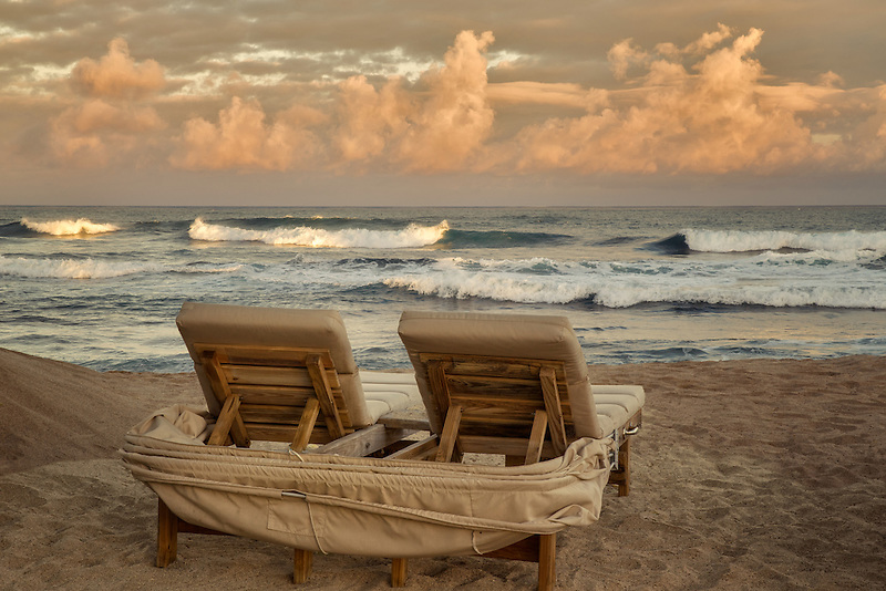 Sunrise and waves with beach chairs. Hawaii, The big Island.