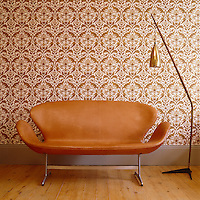 An Arne Jacobsen Swan couch and 1940s German lamp stand against a wall covered in boldly patterned wallpaper by Eley Kishimoto