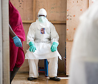 Health care worker Deddeh Y. Miller doffs her PPE at the ELWA II ETU (Ebola treatment unit) in Monrovia, Liberia on Sunday, March 1, 2015. Miller wears her portrait, created as part of Occidental College professor Mary Beth Heffernan's PPE Portrait Project.<br /> (Photo by Marc Campos, Occidental College Photographer) Mary Beth Heffernan, professor of art and art history at Occidental College, works in Monrovia the capital of Liberia, Africa in 2015. Professor Heffernan was there to work on her PPE (personal protective equipment) Portrait Project, which helps health care workers and patients fighting the Ebola virus disease in West Africa.<br />