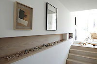 A recessed shelf in a light wood is set into a wall where a collection of natural stones are displayed. Steps beside the wall lead up to a sitting area.