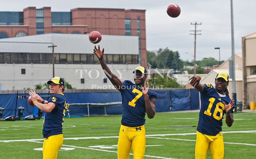 Michigan quarterbacks Tate Forcier (5), Devin Gardner (7), and Denard Robinson (16) throw passes for photographers at the annual NCAA college football media day, Sunday, Aug. 22, 2010, in Ann Arbor, Mich. (AP Photo/Tony Ding)