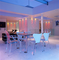 The glass dining table in the centre of the living area was designed by Norman Foster with a pair of transparent dining chairs by Philippe Starck and white chairs by Arne Jacobsen