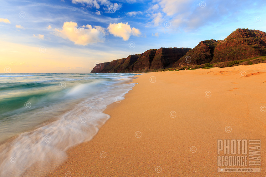 A gentle ocean softly flows onto the golden sand of Polihale Beach at Polihale State Park on the far west side of Kaua'i.