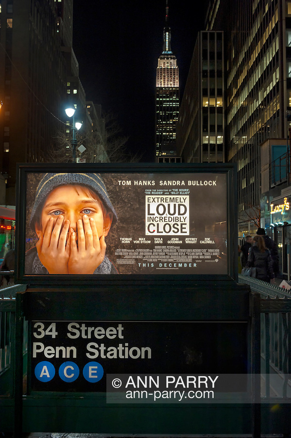 """Manhattan, NY, USA - January 9, 2012: Movie poster """"Extremely Loud & Incredibly Close"""" hangs illuminated at night over Penn Station subway entrance with Empire State Building in background. At stairwell entrance to the MTA (Metropolitan Transit Authority) 34 Street Penn Station subway station. [Fictional movie is set at time of 9/11 terrorist attacks on Twin Towers in NYC.]"""