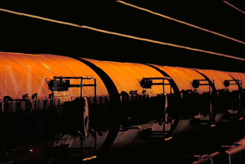 Train tank cars at sunset