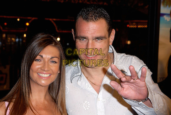 VINNIE JONES & WIFE TANYA.The Big Bounce world premiere held at The Mann Village Theatre in Westwood, California.29 January 2004        .*UK Sales Only*            .waving, hand                                             .www.capitalpictures.com.sales@capitalpictures.com.©Capital Pictures.
