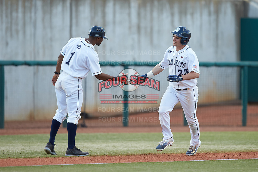 Braxton Giavedoni (23) of the Penn State Nittany Lions slaps hands with assistant coach Andre Butler (1) at third base after a home run against the Xavier Musketeers (1) at Coleman Field at the USA Baseball National Training Center on February 25, 2017 in Cary, North Carolina. The Musketeers defeated the Nittany Lions 7-5 in game two of a double header. (Brian Westerholt/Four Seam Images)